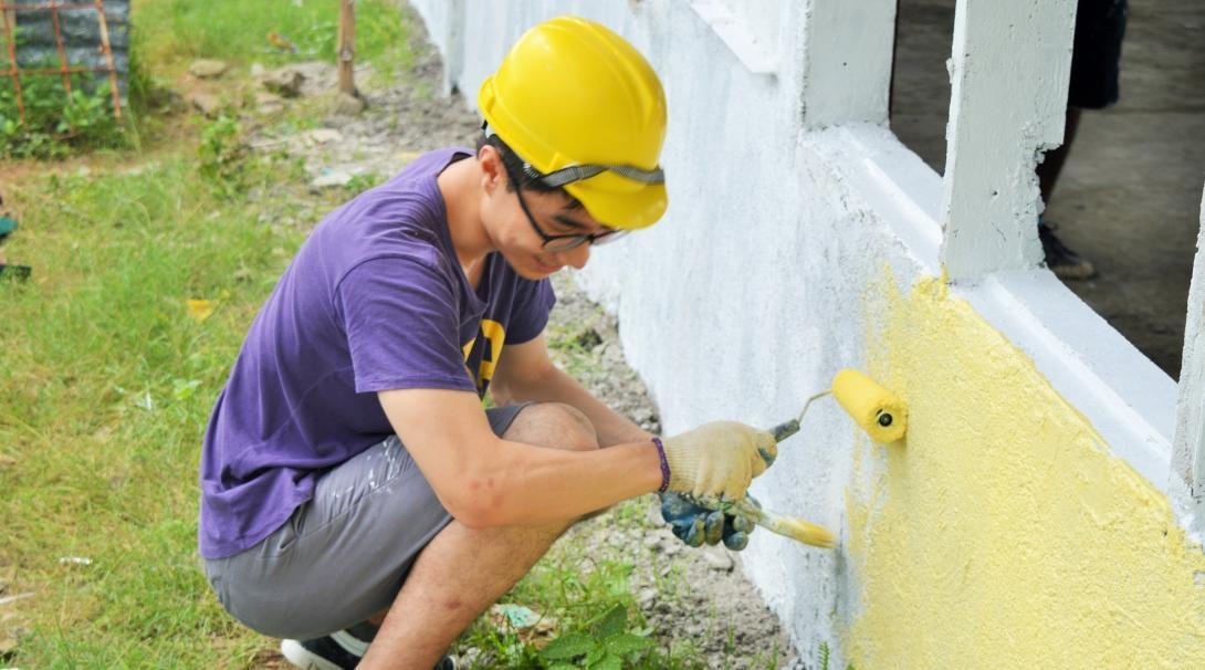 A teenage volunteer doing building work in the Philippines paints the walls of a school yellow.